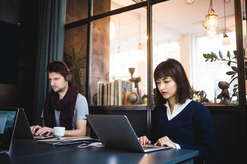 Confident female and male entrepreneurs using laptops at desk in office - MASF11970