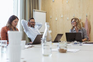 Business colleagues using laptops while sitting at conference table in board room - MASF11988