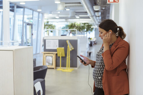 Pregnant businesswoman listening music on smart phone at workplace - MASF12018