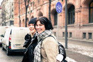 Portrait of cheerful young women wearing warm clothing while standing on street in city during winter - MASF12138