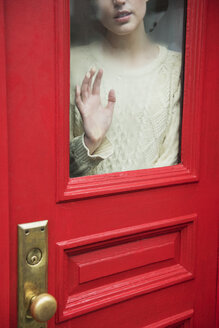 Caucasian woman daydreaming behind red door - BLEF01175