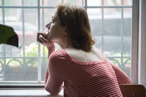 Pensive Caucasian woman daydreaming near window - BLEF01181