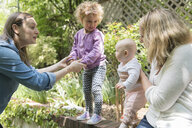 Caucasian mothers holding daughters on garden wall - BLEF01217