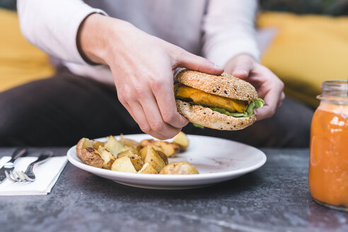 Close-up of man having a vegan burger with potatoes for lunch - FBAF00448