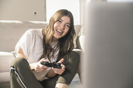 Happy young woman playing video game at home - UUF17250