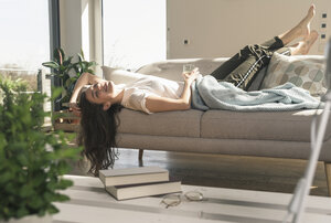 Relaxed young woman lying on couch - UUF17256