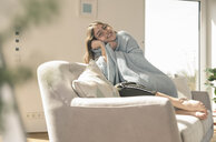 Happy young woman with woolen blanket on couch - UUF17262