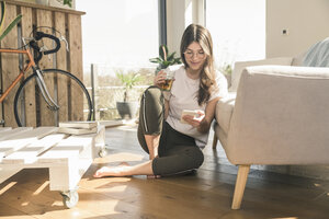 Young woman sitting on the floor at home with drink and cell phone - UUF17268