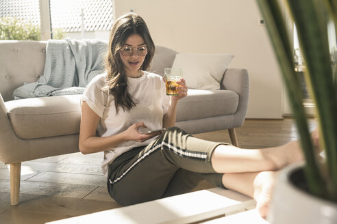Young woman sitting on the floor at home with drink and cell phone - UUF17271