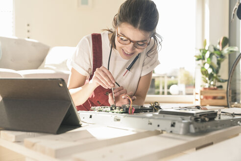 Young woman working on computer equipment at home next to tablet - UUF17277