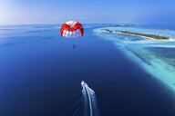 Maledives, South Male Atoll, paraglider flying along an atoll, aerial view - AMF06973