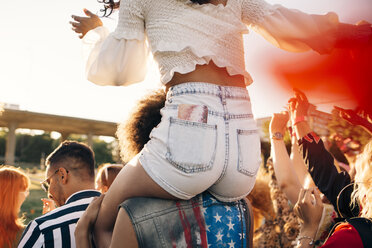 Man carrying friend on shoulder while enjoying at music festival - MASF12171
