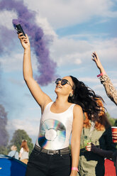 Cheerful woman holding distress flare with purple smoke while enjoying music concert with friends - MASF12204