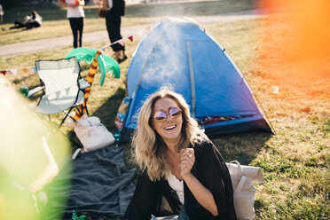 High angle view of cheerful woman wearing sunglasses sitting against tent on field during summer - MASF12222
