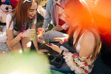 High angle view of friends talking over mobile phone while enjoying at music festival - MASF12225