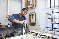 Confident young male craftsperson rubbing sand paper on frame at workshop - MASF12264
