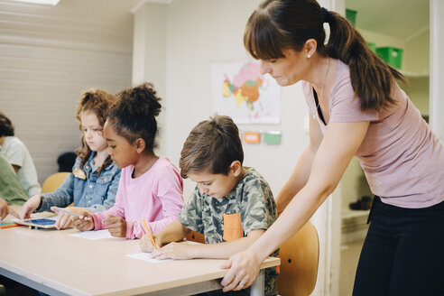 Female teacher assisting students in learning at classroom - MASF12306
