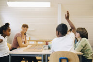 Teacher looking at boy raising hand while answering in classroom - MASF12315