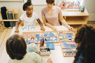 High angle view of teacher teaching spellings to children - MASF12321