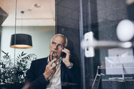 Thoughtful male manager talking on smart phone while looking away at creative office - MASF12342