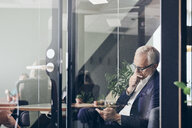 Mature male manager using smart phone seen through glass wall at creative office - MASF12345