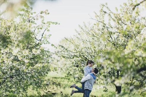 Caucasian man lifting woman under flowering trees - BLEF01263
