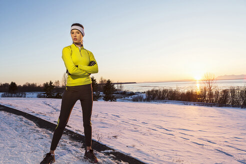 Caucasian runner posing with arms crossed in winter - BLEF01275