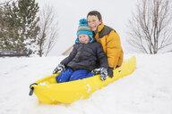 Smiling boys sliding on toboggan on hill in winter - BLEF01299