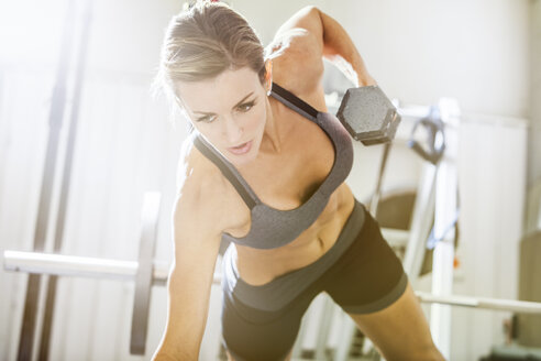 Woman lifting weights in gymnasium - BLEF01302