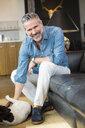 Caucasian man sitting on sofa petting dog - BLEF01311