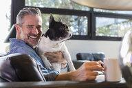 Caucasian man hugging dog on sofa and drinking coffee - BLEF01314