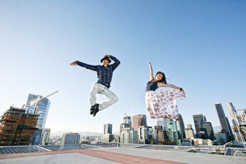 Couple dancing and jumping on urban rooftop - BLEF01335