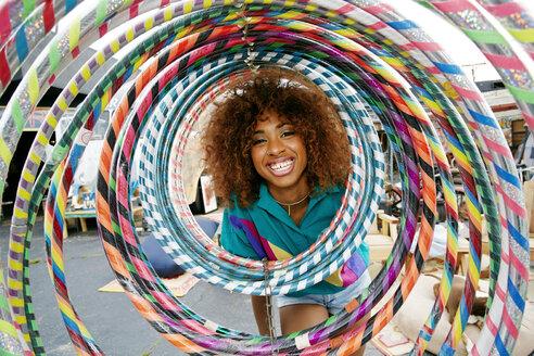 Portrait of smiling black woman behind hoops - BLEF01377