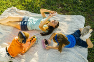 Caucasian brother and sisters laying on blanket in park using technology - BLEF01416