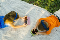Caucasian brother and sister laying on blanket using technology - BLEF01422