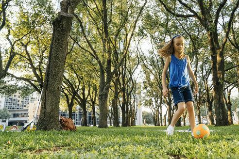 Caucasian girl kicking soccer ball in park - BLEF01440