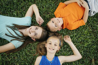 Close up portrait of smiling Caucasian brother and sisters laying on grass - BLEF01446
