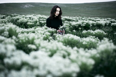 Caucasian woman standing in the field of wildflowers - BLEF01515