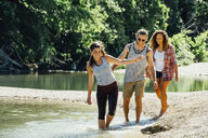 Smiling friends wading in river - BLEF01518