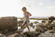 Caucasian girl walking on rocks at beach - BLEF01590