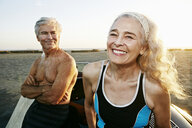 Older Caucasian couple leaning on convertible car at beach - BLEF01758