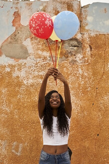Portrait of happy young woman with three balloons - VEGF00094