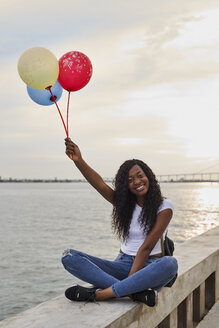 Mocambique, Maputo, portrait of happy young woman with three balloons sitting in front of the sea - VEGF00097