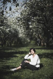 Woman sitting on meadow between apple trees - EYAF00185