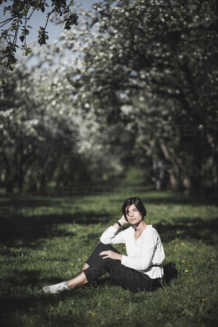 Woman sitting on meadow between apple trees - EYAF00185 - Ekaterina Yakunina/Westend61