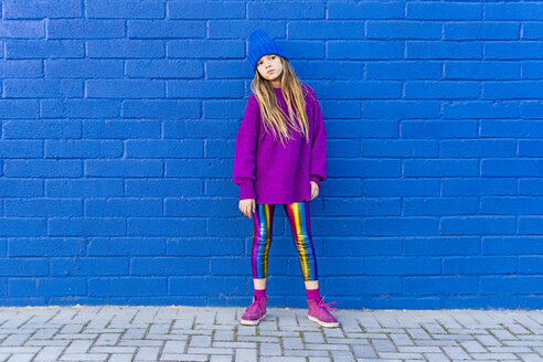 Portrait of girl wearing blue cap and oversized pink pullover standing in front of blue wall - ERRF01195