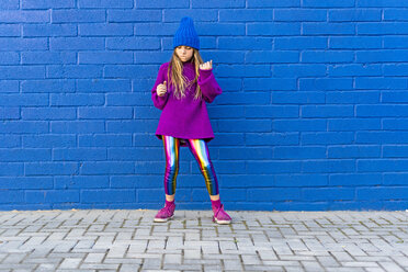 Girl wearing blue cap and oversized pink pullover standing in front of blue wall dancing - ERRF01198
