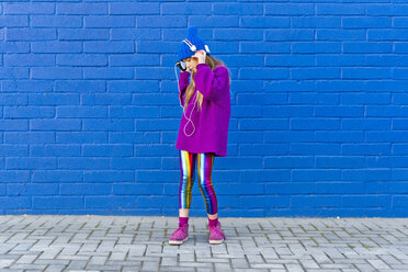 Girl wearing blue cap and oversized pink pullover standing in front of blue wall listening music with headphones - ERRF01201