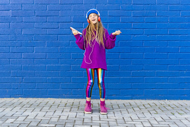 Girl wearing blue cap and oversized pink pullover standing in front of blue wall listening music with headphones - ERRF01204