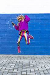 Girl with headphones and smartphone jumping in the air in front of blue wall - ERRF01207